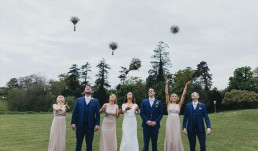 Bride and her bridesmaids and ushers throwing their bouquets in the air