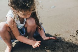 Little girl playing with the sand in family photography shoot at penarth