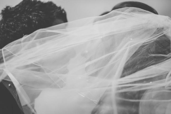 Bride & Groom kissing behind the brides veil