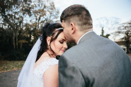 Groom kissing brides forehead on wedding day