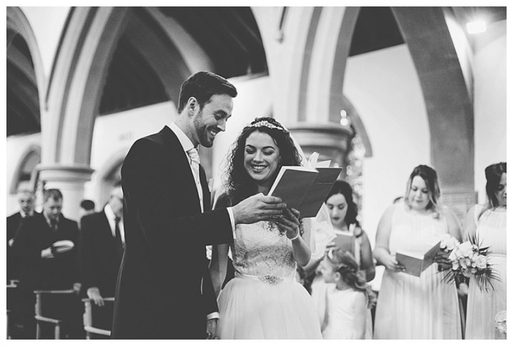 Wedding Photographer Cardiff - Couple singing hymns at their wedding in church