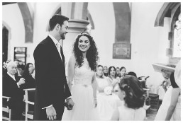Wedding Photographer Cardiff - Newly married couple smiling at church altar
