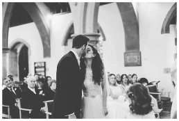 Wedding Photographer Cardiff - Newly married couple kissing at church altar