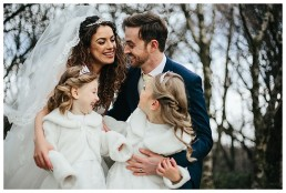 Newly married couple and their kids enjoying playing and laughing in the woods at Cardiff wedding - captured by wedding photographer Cardiff fran