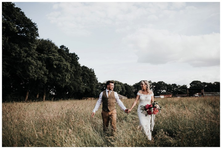 bride and groom taking a romantic stroll in a crop field on a farm in oxford