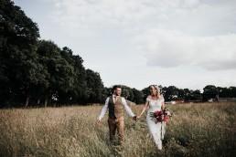 Bride & Groom strolling through the crop field on a farm on their wedding day