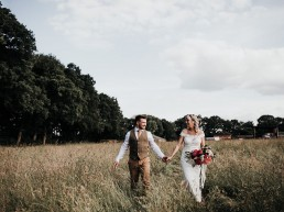 Bride & Groom strolling through the crop field on a farm on their wedding day