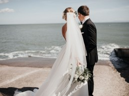 Bride & Groom looking at the waves on Llantwit Major beach