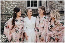 bride and bridesmaids laughing in matching dressing gowns