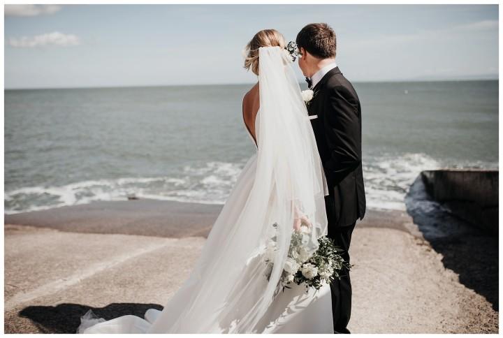 bride and groom posing on llantwit major beach