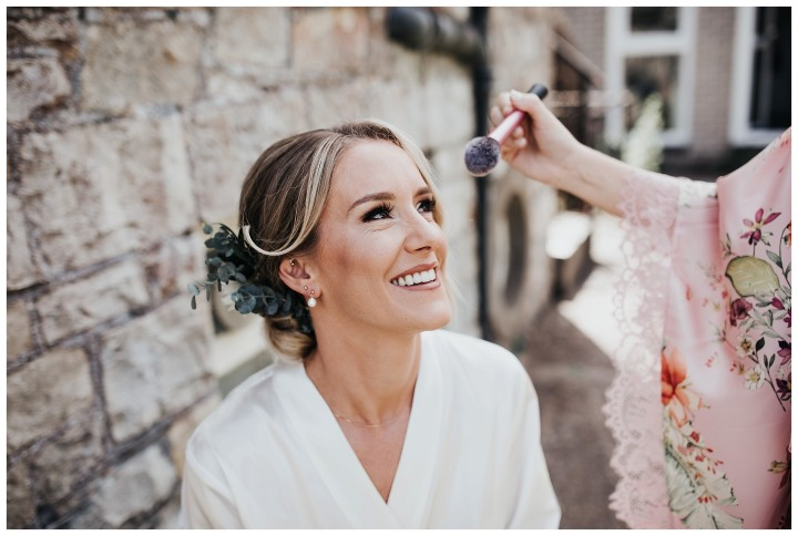 bride getting her makeup done before wedding