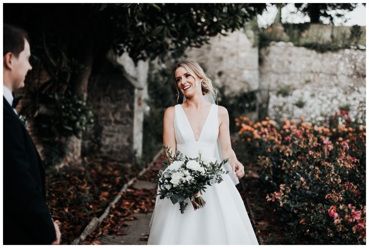 beautiful bride smiling at husband in the walled garden at st donats castle
