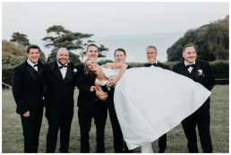 groomsman lifting the bride for a fun group shot at st donats castle