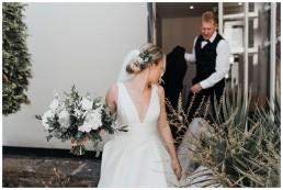 father helping arrange brides train